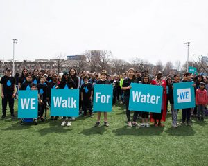 Kids holding signs - We walk for water